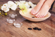 Manicured female feet in spa wooden bowl with flowers and water closeup.  Stock Image