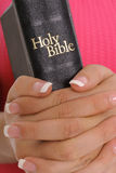 Manicured female hands holding bible. Shot of a manicured female hands holding bible Royalty Free Stock Photography