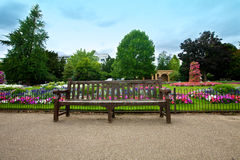 Manicured flower garden with a wooden bench Royalty Free Stock Photos