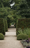 Manicured Garden. A long, shaded pedestrian path leads through a manicured garden Stock Image
