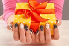 Manicured hands holding gift box. Close up of woman hands with matte manicure holding yellow gift box with red ribbon. Holidays and celebrations concept Royalty Free Stock Image