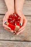 Manicured hands holding little gift box. Young woman hands with beautiful manicure and gift box, old wooden background Royalty Free Stock Photo