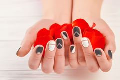 Manicured hands holding red petals. Well-groomed hands with rose petals close up. Nails and hands treatment concept Royalty Free Stock Image