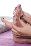 Manicured hands stroke bare feet. Painted with dark nail polish by gray towel on plush purple spa table royalty free stock image