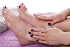 Manicured hands stroke bare feet. Painted with dark nail polish by gray towel on plush purple spa table stock photography