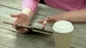 Manicured hands typing text on the tablet. Cardboard cup of hot cappuccino, female hands using digital tablet on vintage wooden table close up stock video footage