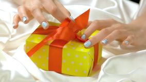 Manicured hands untied ribbon on gift box. Beautiful female hands with perfect winter manicure unpacking yellow gift box on white silk. Holidays and stock video footage