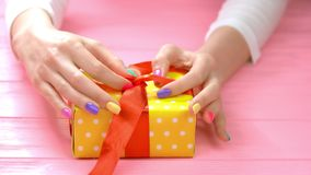Manicured hands untied ribbon on gift box. Young woman hands with summer manicure unpacking box with gift on pink wooden background stock video