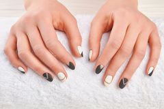 Manicured hands on white towel. Well-groomed female hands in spa salon close up. Hands and nail treatment. Stylish autumn manicure Stock Photos