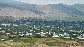 Manicured jordbruksmark och stad i botten av berget arkivfilmer