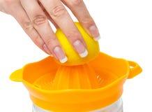 Manicured kvinnligt för citronlimefrukt räcker sammanpressning av ny sund fruktsaft från gul en isolerad citronlimefrukt Royaltyfri Foto