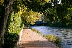 Manicured paved river path. Wide blue river running next to brick paved path in autumn on a sunny day Royalty Free Stock Photos
