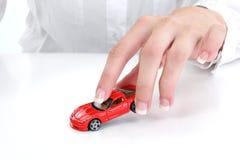 Manicured weibliche Hand, die mit Spielzeug-Auto spielt stockbild