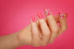 Manicured woman`s nails with pink nailart with flowers. Royalty Free Stock Photo