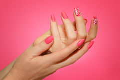 Manicured woman`s nails with pink nailart with flowers. Royalty Free Stock Images