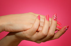 Manicured woman`s nails with pink nailart with flowers. Royalty Free Stock Photos