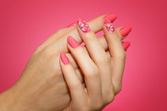 Manicured woman`s nails with pink nailart with flowers. Royalty Free Stock Image