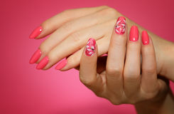Manicured woman`s nails with pink nailart with flowers. Stock Image