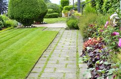 Manicured Yard. A carefully tended garden and walkway in summer splendor Royalty Free Stock Photos