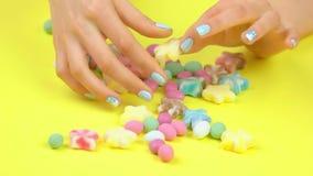 Manicuredhanden en gekleurd suikergoed stock footage