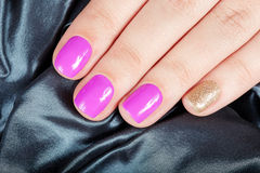 Manicuredspijkers met roze en gouden nagellak worden behandeld dat Royalty-vrije Stock Afbeeldingen
