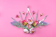 Manicurehulpmiddelen op een roze die achtergrond met bloemen wordt verfraaid stock fotografie