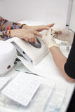 Manicuren som är processaa på kvinnligt, räcker den franska manicuren, danande spikar f8orlängning Arkivfoton