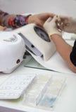Manicuren som är processaa på kvinnligt, räcker slut av boxas upp med konstgjort spikar Arkivfoton