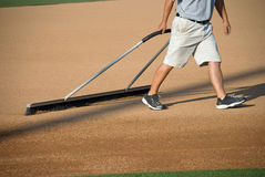 Manicuring the Baseball Field. A young man prepares a baseball field for the game Royalty Free Stock Photography