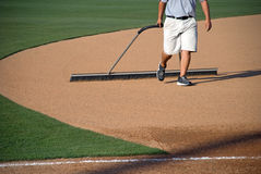 Manicuring the Baseball Field. A young man prepares a baseball field for the game Stock Photo
