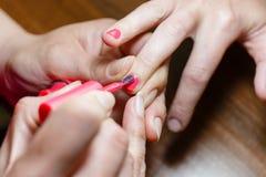 Manicurist красит красную девушку ногтя Стоковое Изображение RF