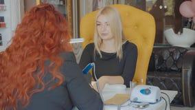 Manicurist прикладывает электрическое сверло пилочки для ногтей к маникюру на женских пальцах Стоковые Фото