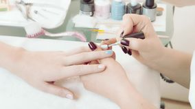 Manicure nail care and polishing. Manicurist applies white nail polish on a girl`s fingernail of a ring-finger in a beauty salon, nail artist covers girl`s nail stock video footage