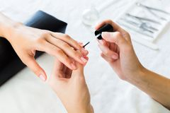 Manicurist applying cuticle softener Royalty Free Stock Photos