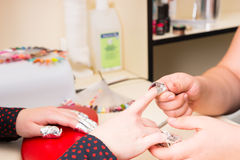 Manicurist Applying Foil Wraps During Manicure. Close Up of Manicurist Applying Foil Wraps to Finger Nails of Female Client During Gel Manicure Treatment in Spa Royalty Free Stock Image