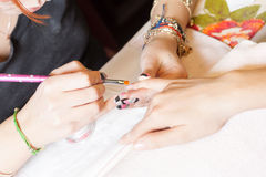 Manicurist applying nail extensions. Manicurist applying liquid acrylic to nail extensions Stock Photos