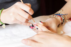 Manicurist applying nail extensions Royalty Free Stock Photography