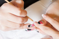 Manicurist applying nail extensions. Professional manicurist applying liquid acrylic to nail extensions Royalty Free Stock Photos