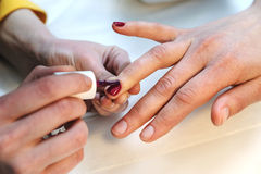Manicurist is applying nail varnish. Stock Photography