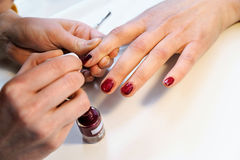 Manicurist is applying nail varnish. Manicurist is applying claret nail varnish on female fingers Royalty Free Stock Photography