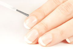 Manicurist applying natural looking nail polish Royalty Free Stock Photography