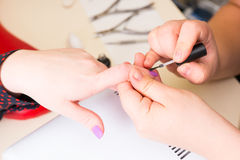 Manicurist Applying Polish to Client Nails. Close Up of Hands of Female Manicurist Applying Polish to Finger Nails of Female Client in Spa Salon Royalty Free Stock Images