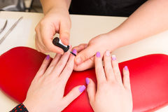 Manicurist Applying Polish to Nails of Client. High Angle View of Manicurist Applying Clear Coat Polish to Finger Nails of Female Client with Hands Resting on Royalty Free Stock Photos
