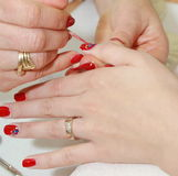 Manicurist applying red nail. Polish on female fingers Royalty Free Stock Photo