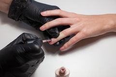 Manicurist black gloves doing a manicure at the beauty salon on a white background. Nail Polish colors Nude. Beautiful. Women`s hands Stock Images