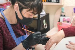 The manicurist in black latex gloves covers the client`s nails with a colored gel polish. In the beauty salon royalty free stock images
