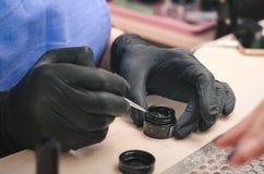Manicurist in black latex gloves dips a brush in black gel polish.  royalty free stock photo