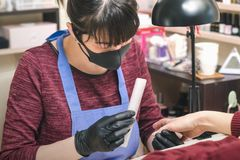 Manicurist in black latex gloves form the shape of a client`s nail in a beauty salon.  stock photography