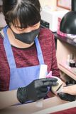 Manicurist in black latex gloves form the shape of a client`s nail in a beauty salon.  royalty free stock photography
