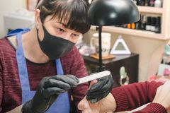 Manicurist in black latex gloves form the shape of a client`s nail in a beauty salon.  stock photo